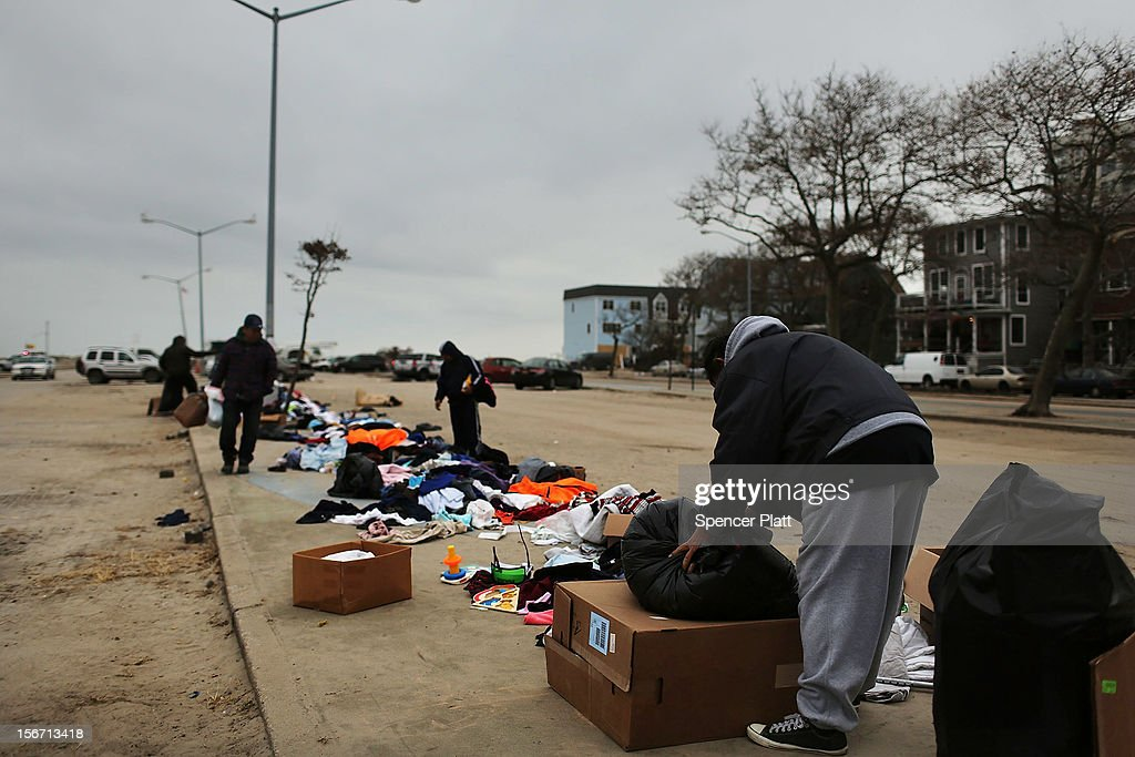 People look through donated clothes in a parking lot of the heavily damaged Rockaway neighborhood, where a large section of the iconic boardwalk was washed away on November 19, 2012 in the Queens borough of New York City. Three weeks after Superstorm Sandy slammed into parts of New York and New Jersey, thousands are still without power and heat.