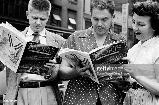 People look through the premiere issue of Sports Illustrated magazine on a Manhattan sidewalk New York New York August 16 1954