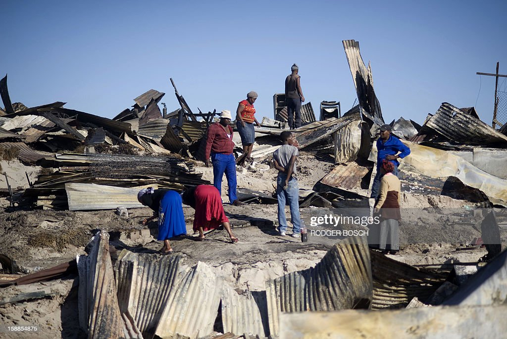 People look through the remains of burnt homes after a fire raged through the BM Informal Settlement, in Khayelitsha, on January 1, 2013, in Cape Town. Several unrelated fires ripped through informal settlements in Cape Town killing at least three people and leaving at least 4,000 homeless on New Year's Day, officials said. AFP PHOTO / RODGER BOSCH