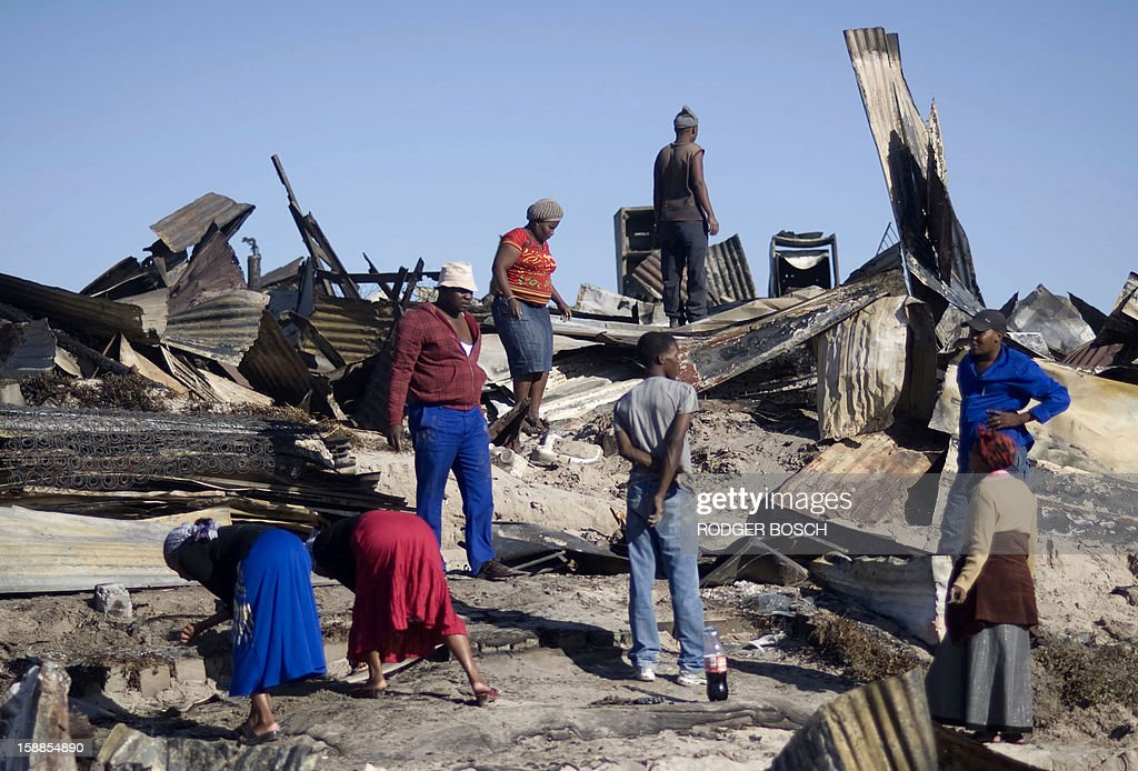 People look through the remains of burnt homes after a fire raged through the BM Informal Settlement, in Khayelitsha, on January 1, 2013, in Cape Town. Several unrelated fires ripped through informal settlements in Cape Town killing at least three people and leaving at least 4,000 homeless on New Year's Day, officials said.