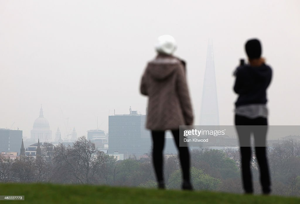 People look through the smog at the London skyline from Primrose Hill on April 3 2014 in London England Dust from the Sahara combined with pollution...