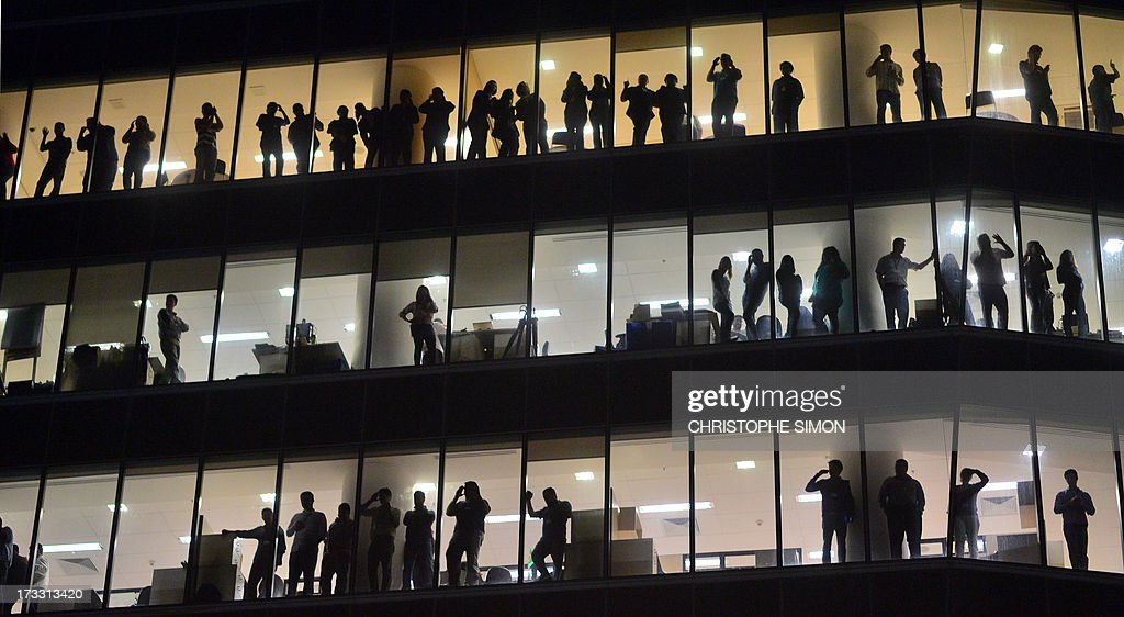 People look through the windows of a building as violent demonstrators clash with the riot police after a march by Brazilian workers in Rio de Janeiro on July 11, 2013 in a day of industrial action called by major unions to press demands for better work conditions. Demonstrators on Thursday blocked roads and staged protest rallies across the country on the 'National Day of Struggles' which was called by the country's five leading labour federations during last month's mass street protests to demand better public services and an end to endemic corruption.