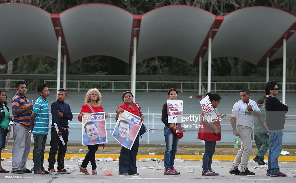 People look toward the camera while waiting in line before the funeral for Venezuelan President Hugo Chavez outside the Military Academy on March 8, 2013 in Caracas, Venezuela. Countless Venezuelans have paid their last respects to Chavez and more than 30 heads of state were expected to attend the funeral today.