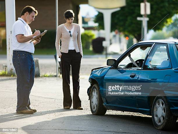 people looking at a car after an accident