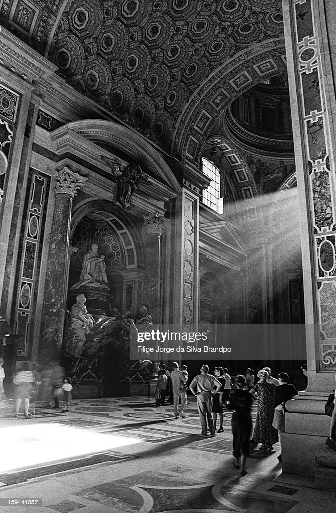 CONTENT] People looking at Alexander VII monument in Saint Peter's Basilica, Vatican City, Rome while beam of light flashes through a window