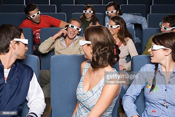 People looking at man using phone in cinema