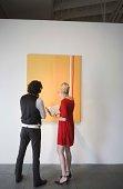 People looking at painting in art gallery