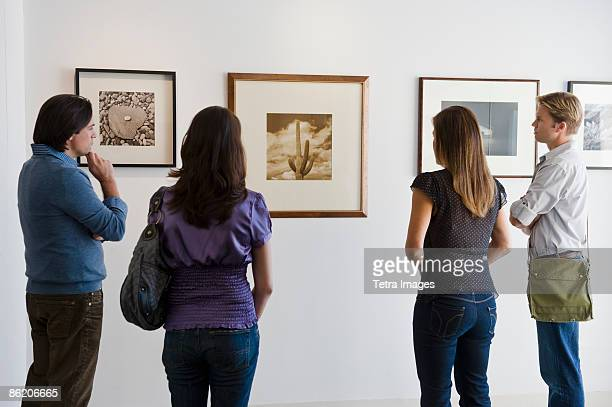 People looking at pictures in art gallery