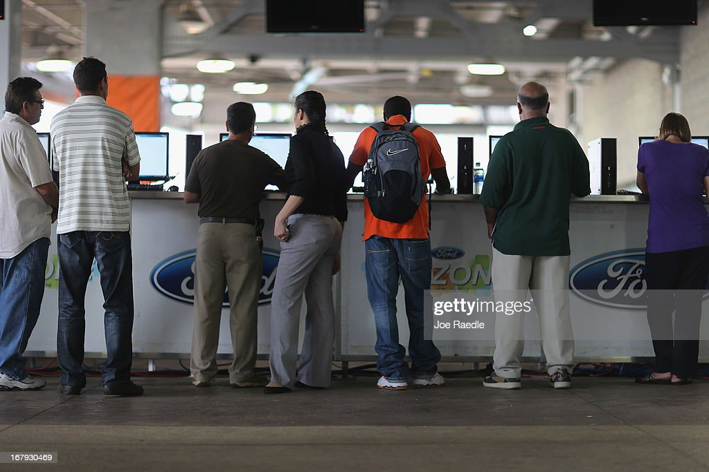 People looking for work apply for jobs using computers set up during a job fair at the Miami Dolphins Sun Life stadium on May 2, 2013 in Miami, Florida. If voters approve a hotel tax hike to fund stadium renovations the jobs would be available. If not, the Dolphins management is indicating they would not be able to renovate the stadium nor create the jobs.