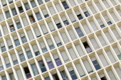 People looking through windows in buildings with abstract architecture and blocks of modern flats dominating the streets during Fete de la Musique on...