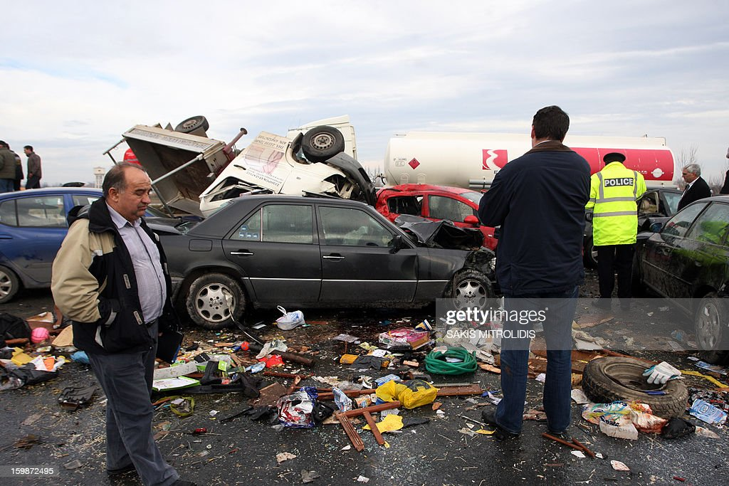 People looks at a pile-up on a highway near Kleidi, some 500 kms north of Athens, on 22 January, 2013. One woman was killed and and another 21 people were injured in the pile-up that occurred due to fog. According the police, 20 vehicles were involved in the first pile-up, both trucks and cars. Among the vehicles involved in the crash was an ambulance bearing a pregnant woman to hospital. AFP PHOTO / Sakis Mitrolidis