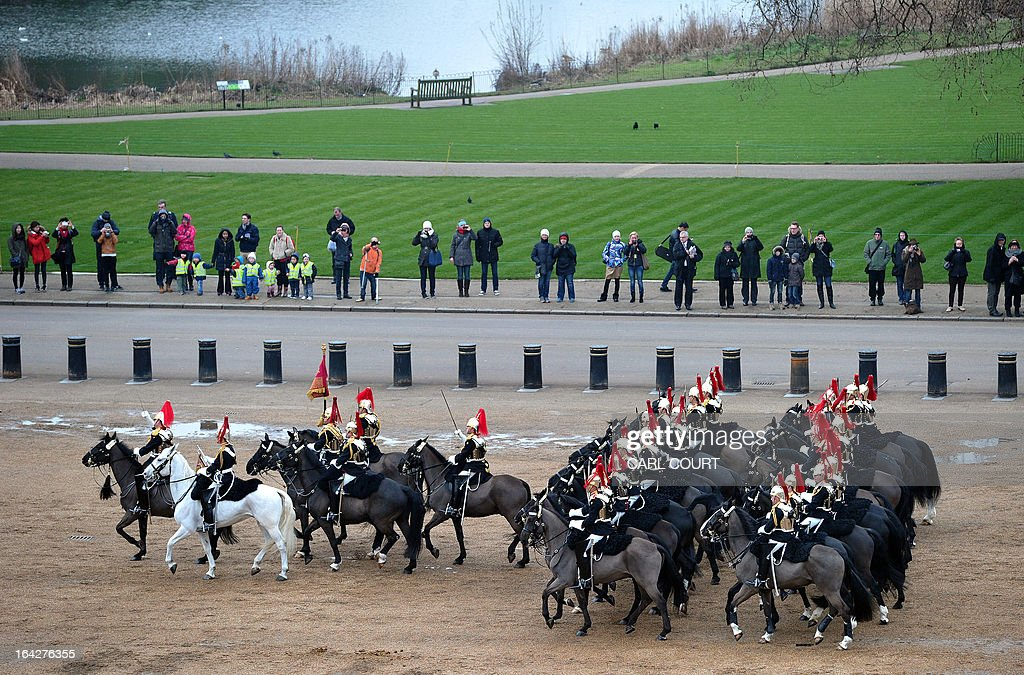 People looks at soldiers from the Household Cavalry Mounted Regiment as they parade on Horse Guards in central London on March 22, 2013 during the Major General's inspection - a test which the unit has to pass in order to participate in state ceremonial duties in 2013.