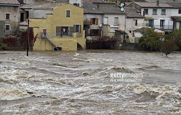 People looks at the Eyrieux river from their house in SaintLaurentduPape after heavy rain on November 4 2014 Heavy rain and gusty winds continued in...