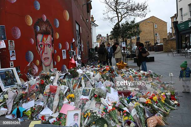 People looks at the writings on the wall near the flowers letters and other items left on a mound continue to grow two weeks after the death of...
