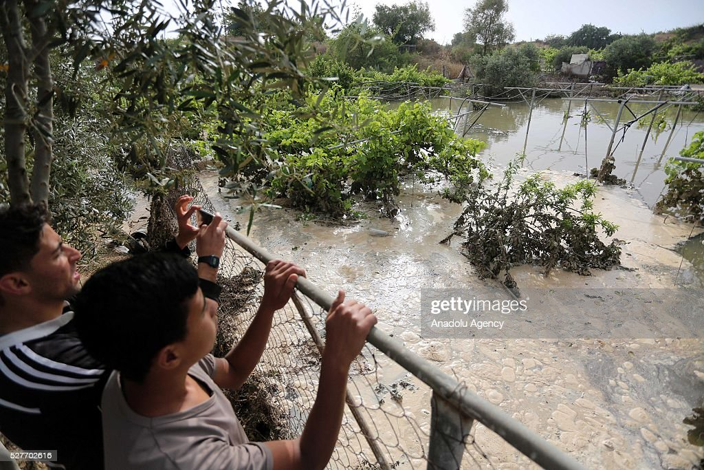 People looks to waste water as a pool belongs to waste water purification plant cracks up and causes damage on the area in Ez-Zeytun neighborhood of Gaza City, Gaza on May 3, 2016.