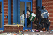 People loot a CVS pharmacy near the corner of Pennsylvania and North avenues during violent protests following the funeral of Freddie Gray April 27...