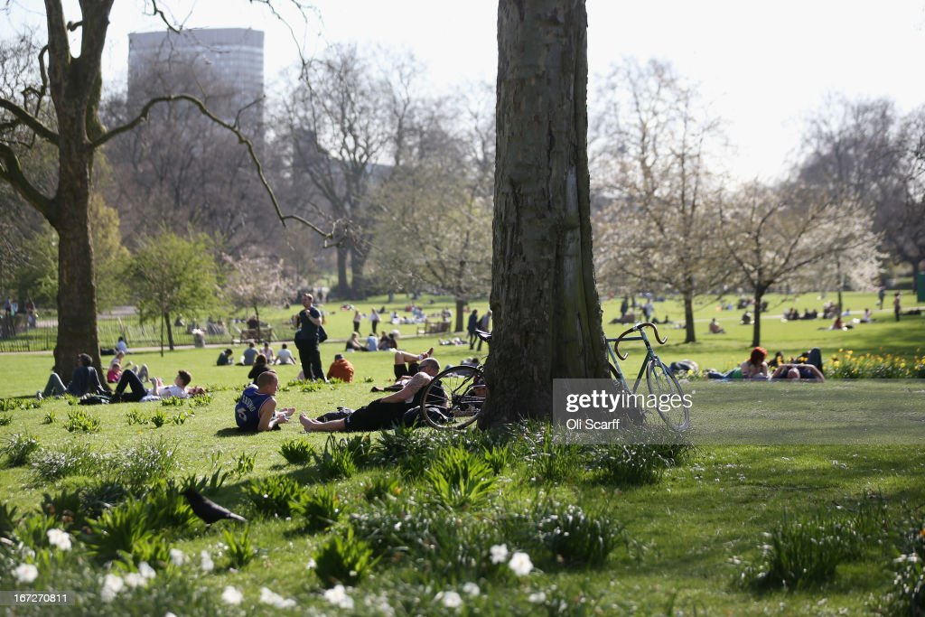 People lounge in the grass in the warm Spring weather in St James's Park on April 23, 2013 in London, England. Following an unseasonably cold start to 2013 temperatures across the UK are beginning to increase.