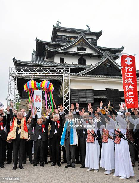 People make banzai cheers in front of the main tower of the Matsue Castle after the Agency for the Cultural Affairs recommended to the Education...