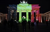 People make photos as the colors of the Belgian flag are projected on to the Brandenburg Gate in Berlin as the German capital shows its solidarity...