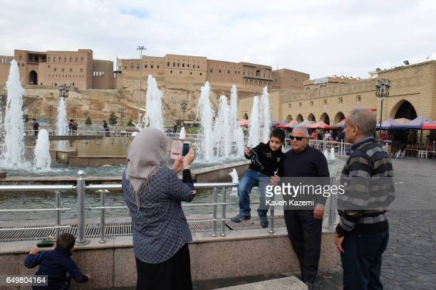 People make souvenir pictures in the square near the citadel on November 2 2016 in Erbil Iraq Erbil also spelt Arbil or Irbil is the capital city of...