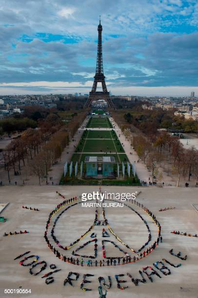 TOPSHOT People make the 'Pray for Paris' sign along with the slogan '100 percent renewable' in Paris on December 6 2015 on the sidelines of the COP21...