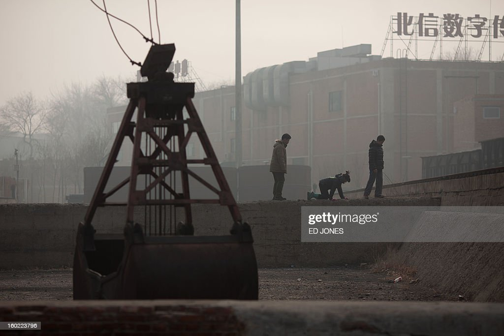 People make their way across a wall at the site of a de-comissioned factory in the 798 art district, during heavy pollution on January 28, 2013. The US embassy air quality index twitter feed recorded levels classed as 'hazardous', with a figure of 493 -- almost 20 times the World Health Organisation's safe limit. AFP PHOTO / Ed Jones