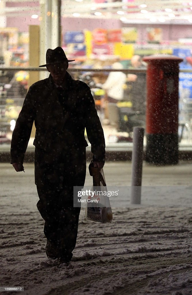 People make their way across Tesco's supermarket car park as more snow falls on January 22, 2013 in Somerset, England. Fresh snow has brought fresh disruption to parts of the UK.
