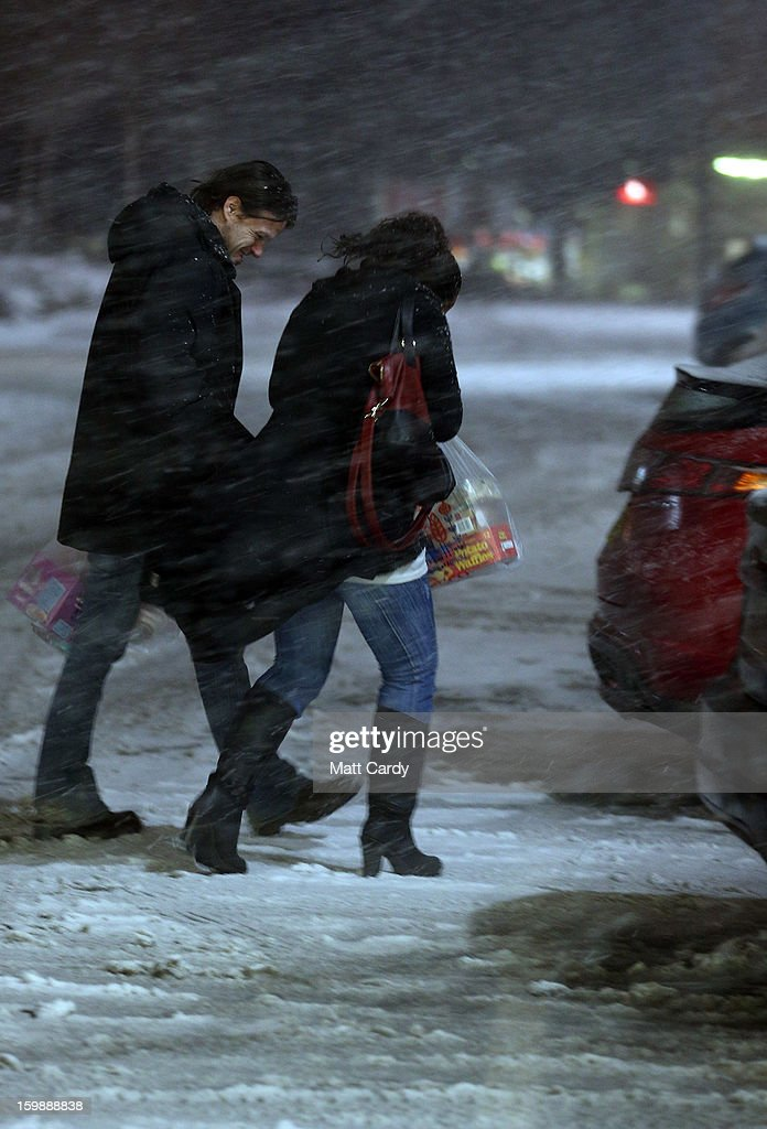 People make their way across Tesco's supermarket car park as more snow falls in Shepton Mallet on January 22, 2013 in Somerset, England. Fresh snow has brought fresh disruption to parts of the UK.