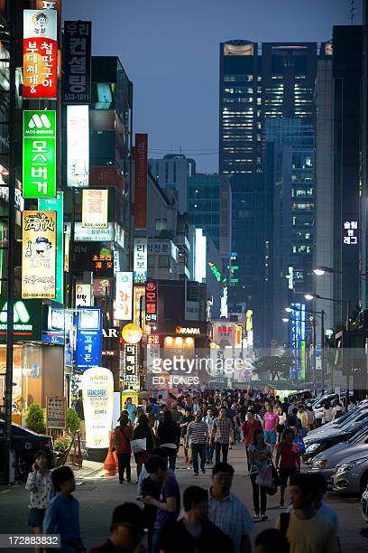 People make their way along a street in the Gangnam district of Seoul on July 5 2013 One of Asia's most affluent countries South Korea is the...