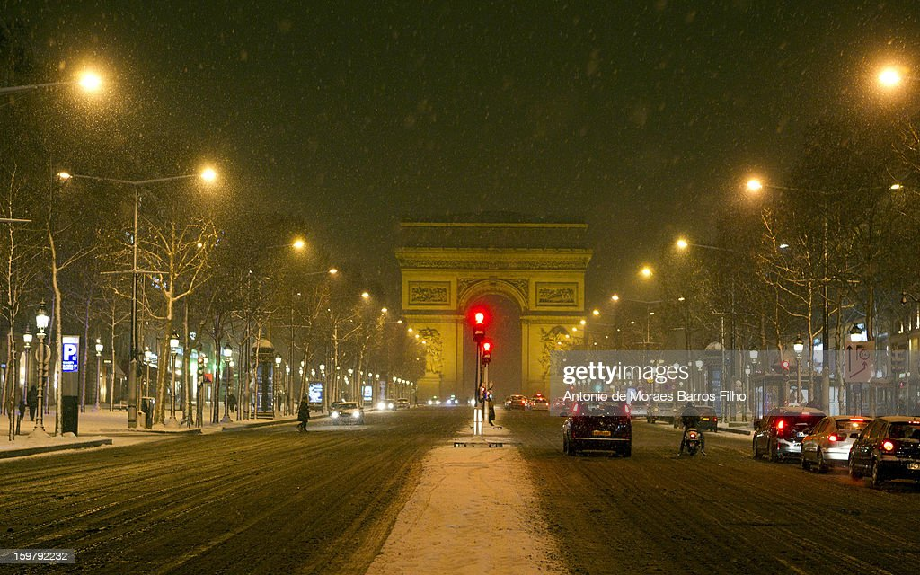 People make their way along the Champs-Elysees as snow falls on January 20, 2013 in Paris, France. Heavy snowfall fell throughout Europe and the UK causing travel havoc and white layers of pretty scenery.