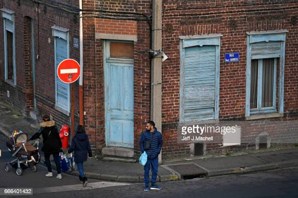 People make their way down a street of terraced houses on February 15 2017 in Henin Beaumont France The former mining town in northern France Henin...