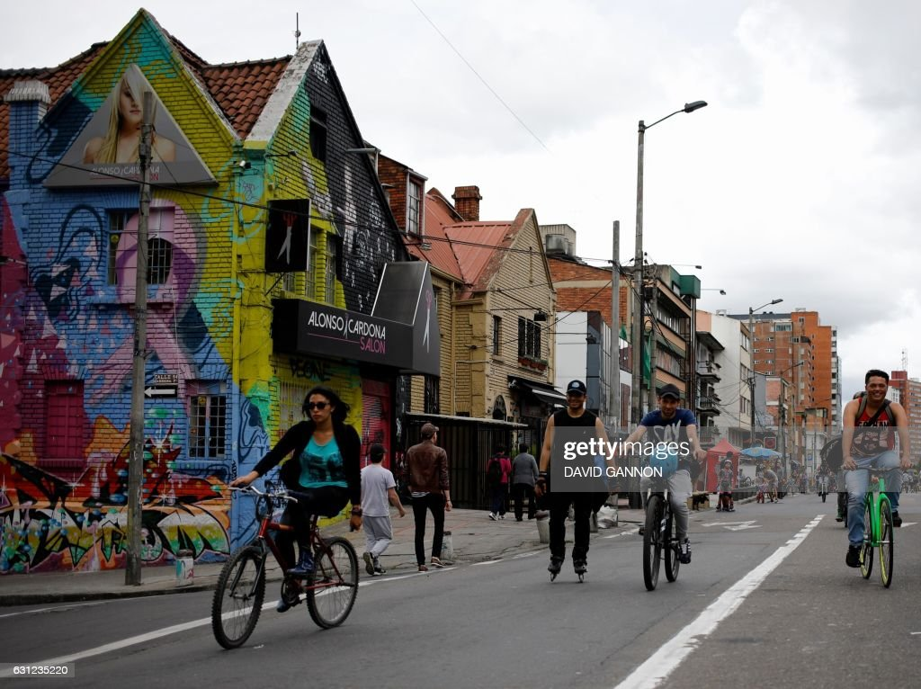 People make their way down a street which is closed off to traffic to allow the public to jog, cycle and skate through the Chapinero district of Bogota, Colombia on January 8, 2017. / AFP PHOTO / David GANNON