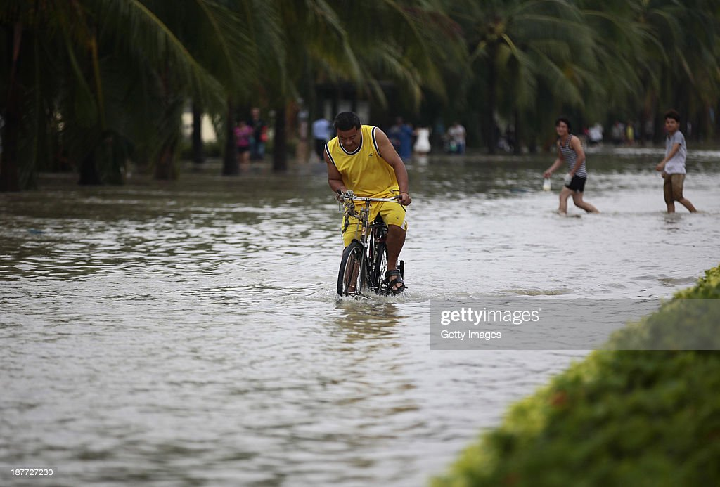 People make their way in a flooded street on November 11, 2013 in Sanya, China. Typhoon Haiyan, which left a trail of destruction in the Philippines, weakened into a tropical depression and brought gales and rainstorms to South China on Sunday.