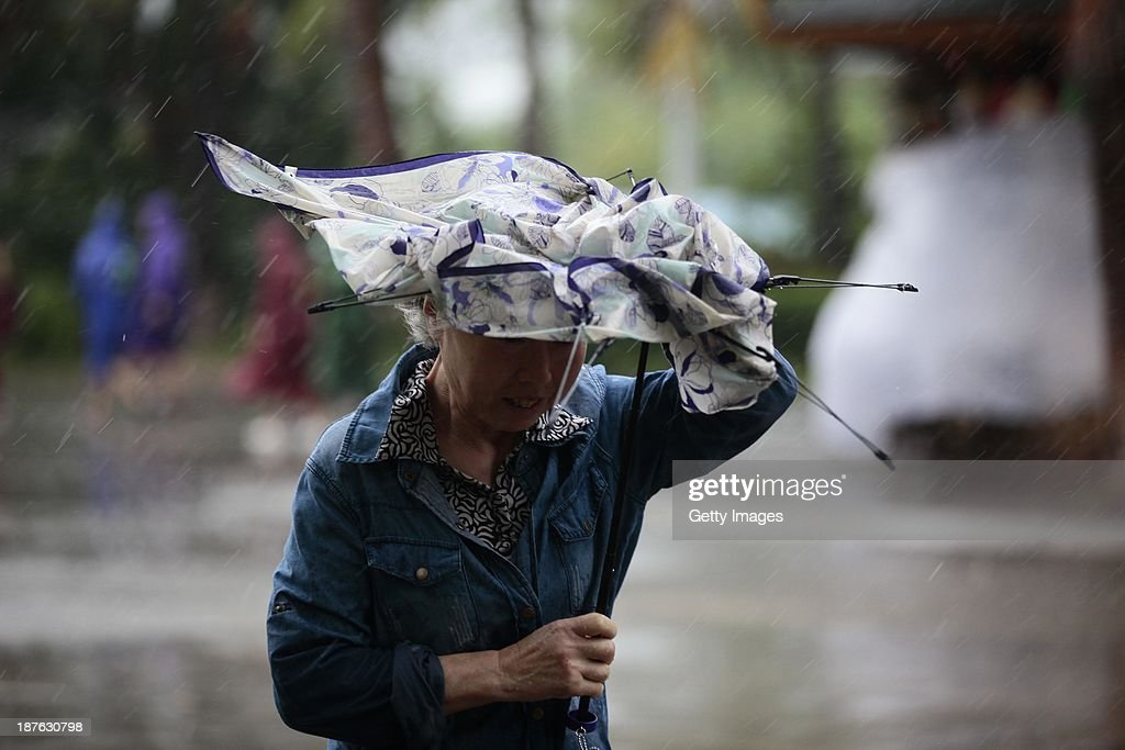 People make their way in the strong wind triggered by Typhoon Haiyan on November 10, 2013 in Sanya, China. Typhoon Haiyan, now categorized as a tropical depression, brought strong winds and rainstorms to South China on Sunday.