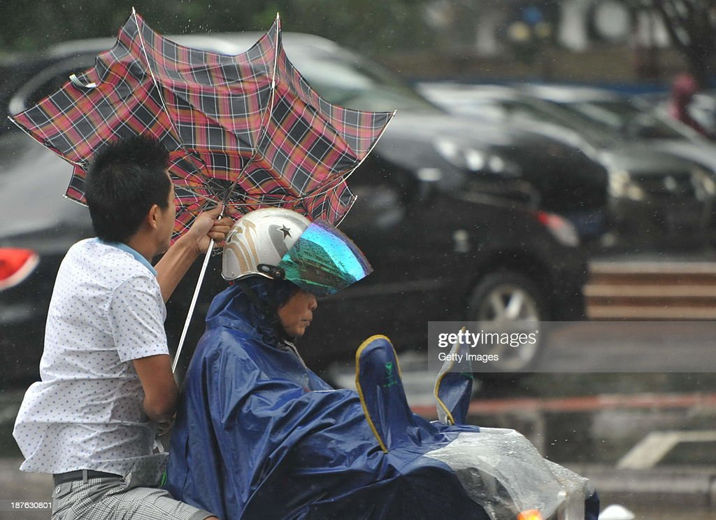 People make their way in the strong wind triggered by Typhoon Haiyan on November 10, 2013 in Qionghai, China. Typhoon Haiyan, now categorized as a tropical depression, brought strong winds and rainstorms to South China on Sunday.