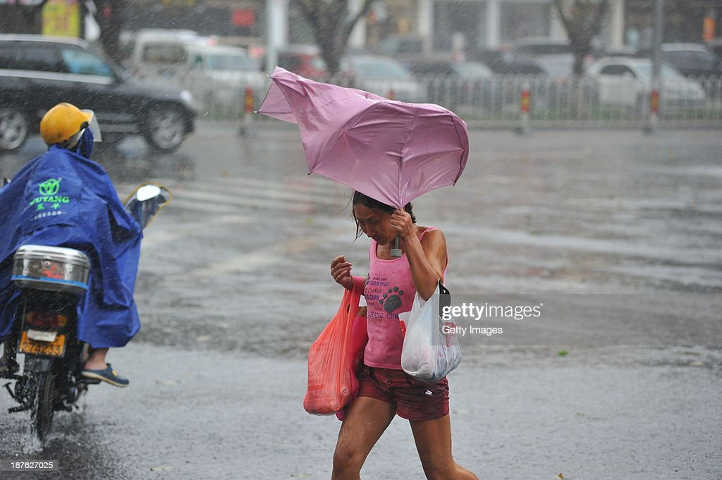 People make their way in the strong winds triggered by Typhoon Haiyan on November 10, 2013 in Haikou, China. Typhoon Haiyan, now categorized as a tropical depression, brought strong winds and rainstorms to South China on Sunday.