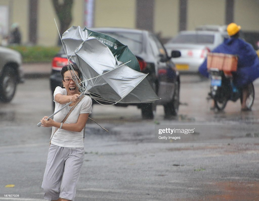 People make their way in the strong winds triggered by Typhoon Haiyan on November 10, 2013 in Qionghai, China. Typhoon Haiyan, now categorized as a tropical depression, brought strong winds and rainstorms to South China on Sunday.