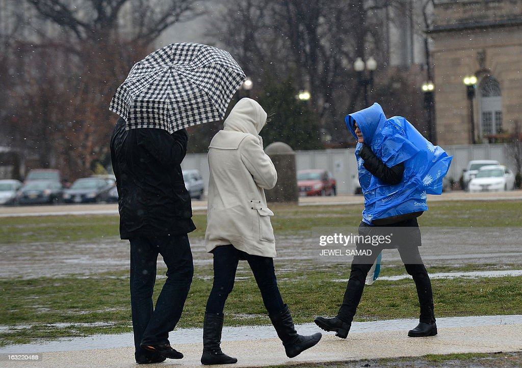 People make their way near the US Capitol during a snow storm in Washington, DC, on March 6, 2013. A massive winter storm pounding the northern US on March 6, grounded 2,600 flights, closed hundreds of schools and made roadways and highways impassible. At least four people were reportedly killed in accidents on icy and snow covered roads and highways. AFP PHOTO/Jewel Samad
