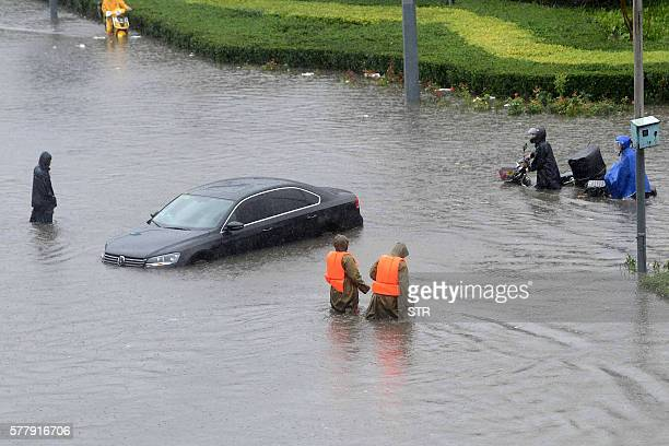 People make their way through a flooded street in Beijing on July 20 2016 At least one person was killed and 34 missing as torrential rain pounded...