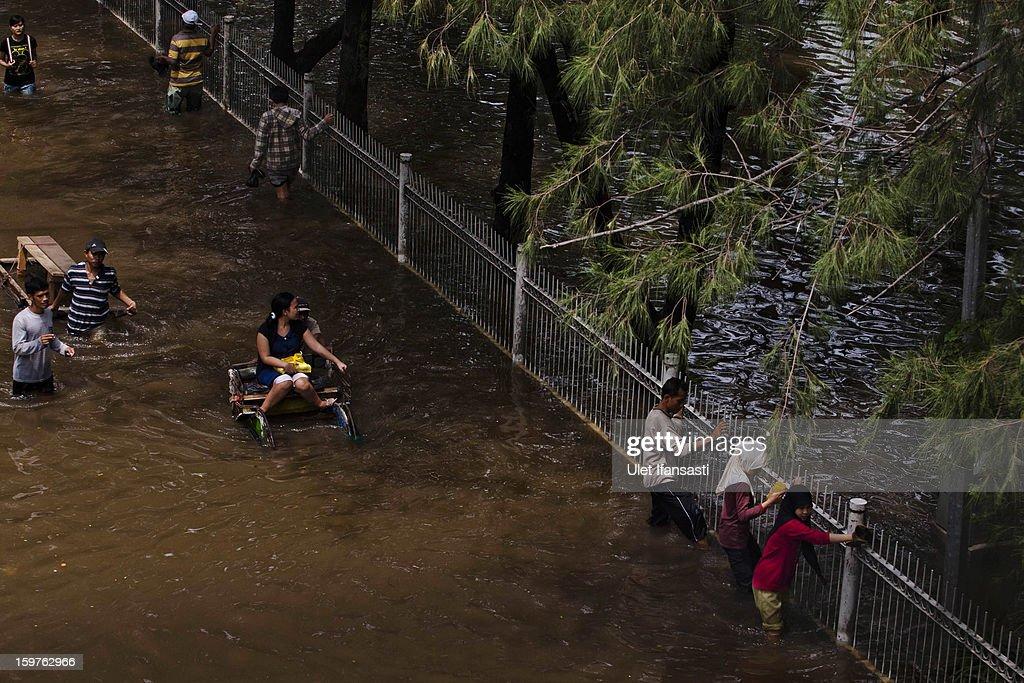 People make their way through floodwaters as major floods hit North Jakarta on January 20, 2013 in Jakarta, Indonesia. The death toll has risen to at least 21 since severe flooding struck the city on January 17. The US has offrered US$150,000 (Rp 1.44 billion) in aid.