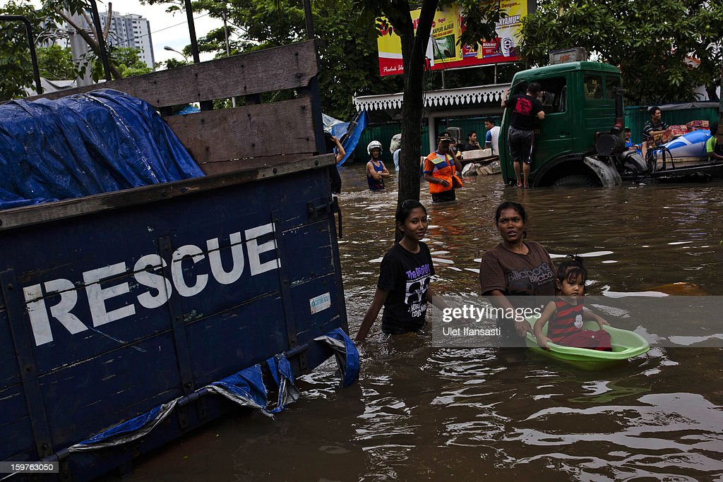 People make their way through floodwaters as major floods hit North Jakarta on January 20, 2013 in Jakarta, Indonesia. The death toll has risen to at least 21 since severe flooding struck the city on July 17. The US has offrered US$150,000 (Rp 1.44 billion) in aid.