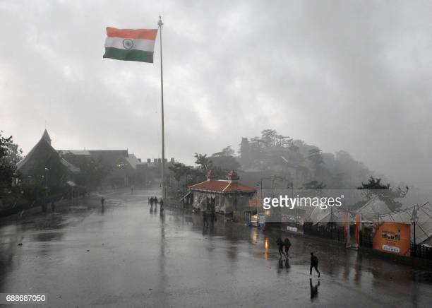 People make their way through heavy rainfall in the northern Indian hill town of Shimla on May 26 2017 / AFP PHOTO /