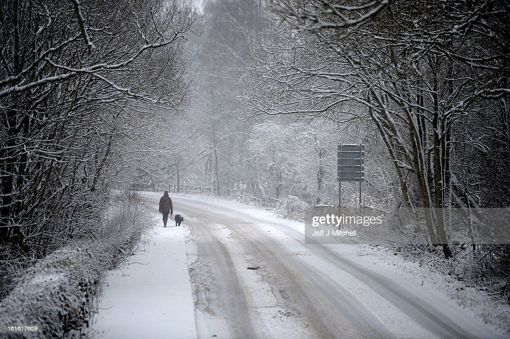 People make their way through recent snowfall on February 13, 2013 in Blanefield, Scotland. Weather forecaster have issued a yellow weather warning of up to 10cm of snow on higher routes, with the possibility of travel disruption.