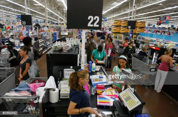 People make their way through the checkout as they make purchases at a WalMart Store August 14 2008 in North Miami Florida The company reported its...