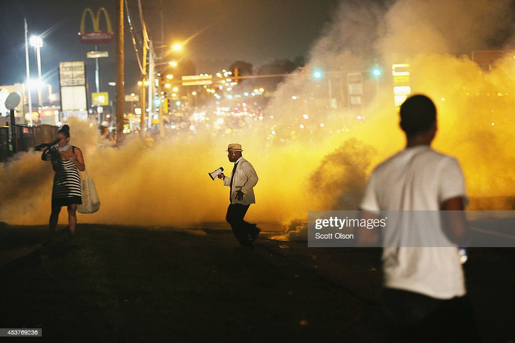 People make their way through the haze as tears gas fills the street during a demonstration over the killing of teenager Michael Brown by a Ferguson police officer on August 17, 2014 in Ferguson, Missouri. Despite the Brown family's continued call for peaceful demonstrations, violent protests have erupted nearly every night in Ferguson since his death.