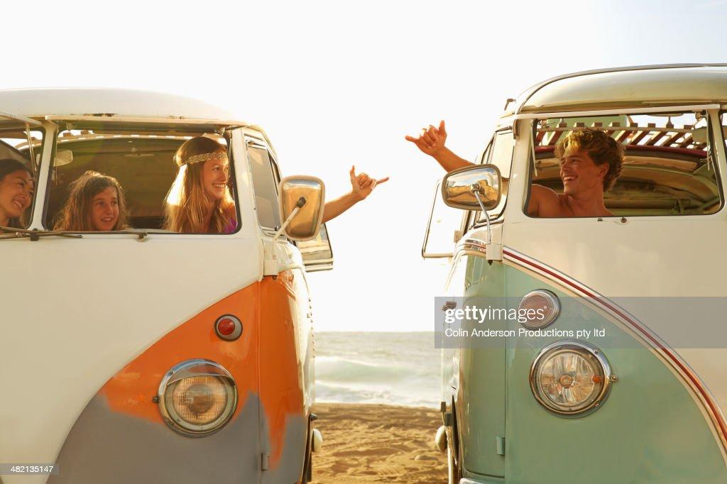 People making hand gestures in vans on beach