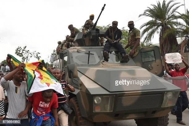 People march alongside a Zimbabwean armoured personnel carrier as a demonstration marches towards the Zimbabwean State House while calling for the...