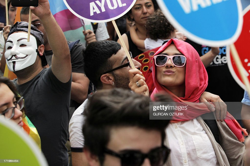 People march and chant slogans during a gay parade on Istiklal Street, the main shopping corridor on June 30, 2013 in Istanbul during the fourth Trans Pride Parade as part of the Trans Pride Week 2013, which is organized by Istanbul's 'Lesbians, Gays, Bisexuals, Transvestites and Transsexuals' (LGBTT) solidarity organization.