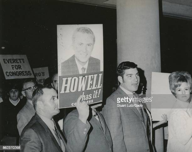 People march at North Carolina State University Raleigh North Carolina holding posters reading Everett for Congress and Howell Has It likely...