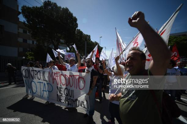 People march behind a banner 'No Tap' against the Trans Adriatic Pipeline during a demonstration on the second day of a G7 summit of Finance...